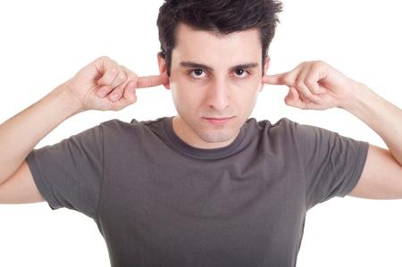 personas escuchando: Retrato de hombre joven guapo con los dedos en los o�dos no escucha expresi�n (aislada sobre fondo blanco) Foto de archivo