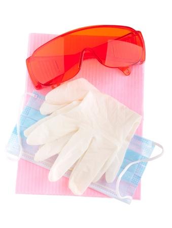 babero: equipos de salud y seguridad (gafas, guantes, m�scara y Peto) para prevenir la infecci�n cruzada (aislada en blanco) Foto de archivo