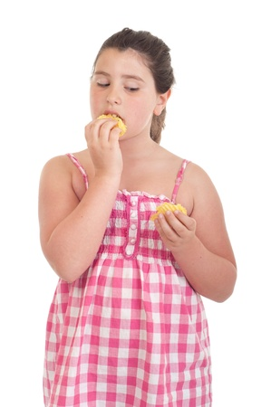 obese child: cute little girl with hungry expression eating chips (isolated on white background)