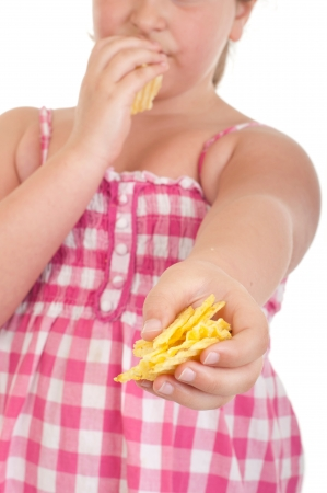 obese child: little girl eating chips and offering some too (isolated on white background)