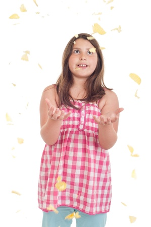 overweight child: excited little girl trying to catch falling chips (isolated on white background)