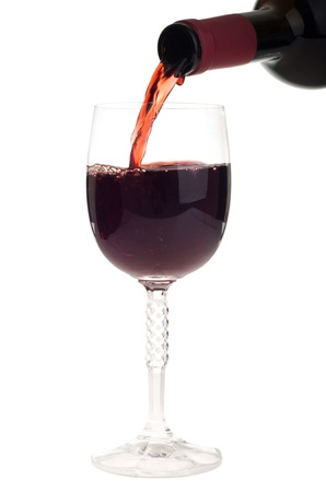 alcoholic beverages: bottle pouring red wine into a crystal glass (isolated on white background)