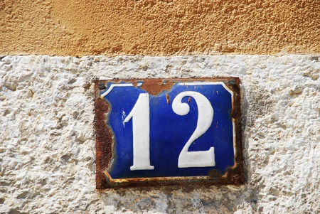 12: blue and white rusty metallic number (12) hanging on stone wall