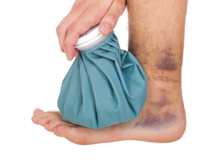 sprain: young male icing a sprained ankle with ice pack (isolated on white background) Stock Photo