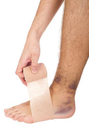 contusion: young male with sprained ankle applying medical bandage (isolated on white background)