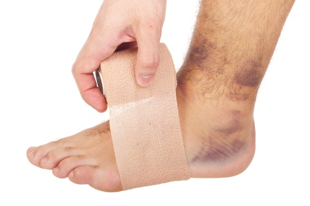 sprain: young male with sprained ankle applying medical bandage (isolated on white background)