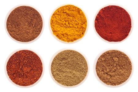 coriandrum sativum: colecci�n de especias Indias (comino, cilantro, piment�n, garam masala, c�rcuma, copos de pimienta roja) en copas de vidrio aislados en fondo blanco Foto de archivo