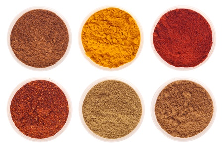 collection of indian spices (cumin, coriander, paprika, garam masala, curcuma, red pepper flakes) on glass cups isolated on white background Stock Photo