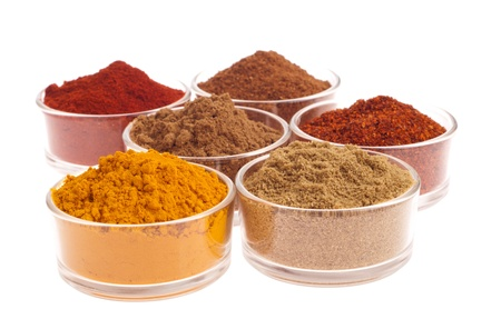 curry spices: collection of indian spices (cumin, coriander, paprika, garam masala, curcuma, chili powder) on glass cups isolated on white background