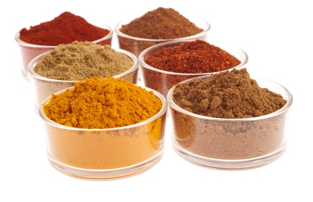 collection of indian spices (cumin, coriander, paprika, garam masala, curcuma, chili powder) on glass cups isolated on white background photo