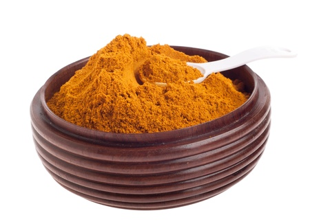 curry powder, mix of indian spices on a vintage wooden bowl with spoon (isolated on white background) Stock Photo - 9728835