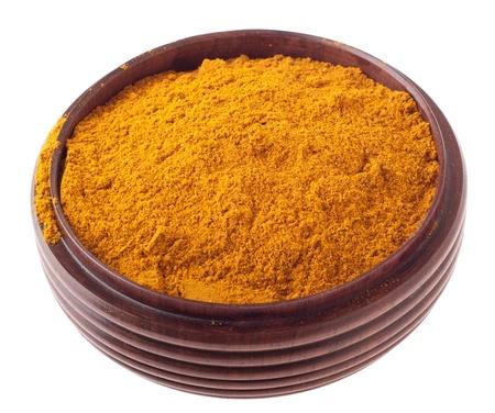 indian spices: Curry poeder, mix van indiaanse kruiden op een vintage houten kom (geïsoleerd op een witte achtergrond)