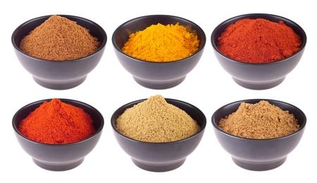 especias: colecci�n de especias Indias (comino, cilantro, piment�n, garam masala, c�rcuma, polvo de chili) en tazas de cer�micas negras aisladas sobre fondo blanco