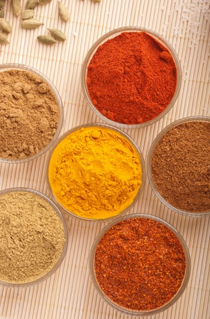piri: gorgeous setting with indian cooking spices (cumin, coriander, paprika, chili powder, piri piri, turmeric) on a wooden mat Stock Photo