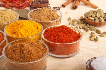 gorgeous setting with cooking spices and herbs (bay leaves, cumin, coriander, chili powder, cloves, cardamom pods, cinnamon sticks, paprika, piri piri, salt, turmeric) on a wooden mat (shallow DOF) photo
