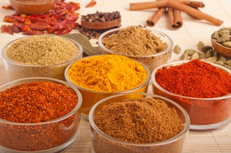 indian spices: prachtige omgeving met koken specerijen en kruiden (laurierbladeren, komijn, koriander, chilipoeder, kruidnagel, kardemom peulen, kaneelstokjes, paprika, piri piri, zout, kurkuma) op een houten mat (ondiepe DOF) Stockfoto