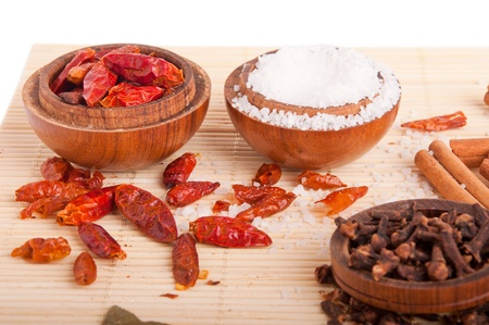 piri: gorgeous setting with cooking spices and herbs (cloves, cinnamon sticks, piri piri, salt) on wooden bowls and mat (isolated on white)
