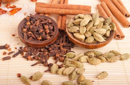 piri piri: gorgeous setting with cooking spices and herbs (cloves, cardamom pods, cinnamon sticks, piri piri) on a wooden mat