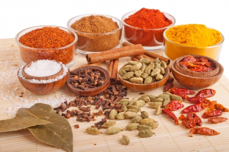 indian spice: gorgeous setting with cooking spices and herbs (bay leaves, chili powder, cloves, cardamom pods, cinnamon sticks, garam masala, paprika, piri piri, salt, turmeric) on a wooden mat (isolated on white background)