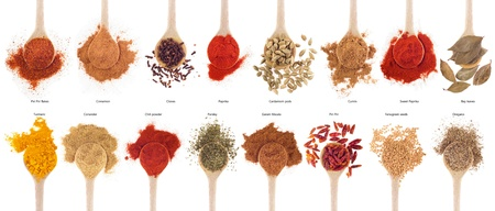 curry spices: gorgeous collection of 16 spices on wooden spoons (cumin, coriander, cloves, curry, chili, piri piri, cinnamon, cardamom, fenugreek,  garam masala, oregano, parsley, paprika, turmeric, bay) isolated on white background