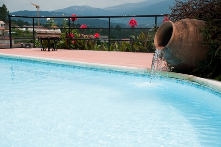 pool side: beautiful swimming pool detail with a ceramic terracota vase as a cascade Editorial