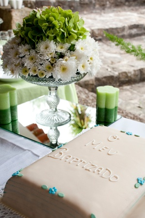 beautiful baptism or christening cake with a gorgeous flowers arrangement and candles (all in green colours) Stock Photo - 9966733