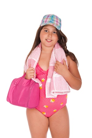 beautiful brunette teenage girl in swimsuit ready for the beach or pool with bag, cap and towel (isolated on white background) photo