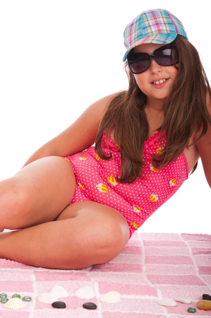 beautiful brunette teenage girl in swimsuit at the beach wearing sunglasses (studio setting with towel and pebbles, isolated on white background) photo
