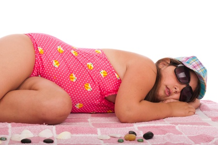 beautiful brunette teenage girl in swimsuit sleeping at the beach (studio setting with towel and pebbles, isolated on white background) Stock Photo - 10055533