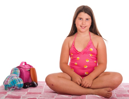 beautiful brunette teenage girl in swimsuit at the beach (studio setting with bag, cap, towel, sun lotion, sunglasses) isolated on white background Stock Photo - 10055372