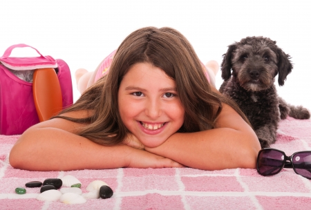 dog rock: smiling brunette teenage girl in swimsuit at the beach with her shipoo dog (studio setting with beach and personal items) isolated on white background