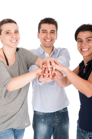 happy smiling brother and sisters putting their hands on top of each other celebrating their union or recent success (isolated on white background) focus on man Stock Photo - 10055423