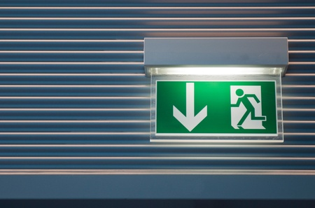 illuminated green emergency exit sign on a modern wall   photo