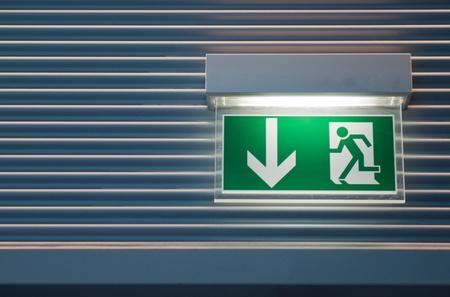 salida de emergencia: signo de salida de emergencia verde iluminada en una pared moderna   Foto de archivo