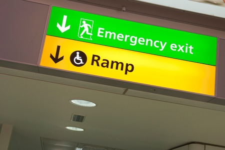 wheelchair access: emergency exit and handicapped ramp sign at a international airport corridor Stock Photo
