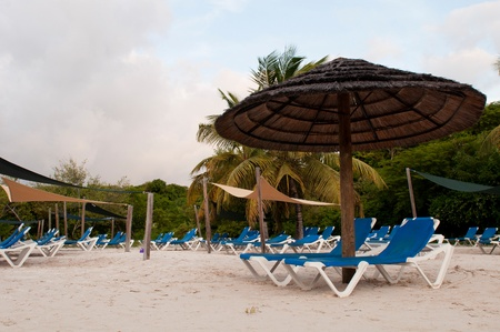 beach chairs and umbrella on a tropical beach resort in Antigua (sunset picture) photo