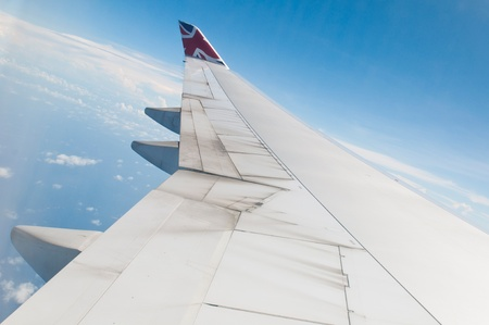 ST JOHNS, ANTIGUA - AUGUST 17: view of Boeing 747 wing of Virgin Atlantic Airways with blue sky clouds close to V. C. Bird International Airport in Antigua on August 17, 2011 in St. John Stock Photo - 10559410