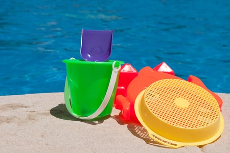 toy fish: bright and colorful children toys at poolside (family vacations concept) Stock Photo