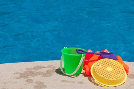 playtime: bright and colorful children toys at poolside (family vacations concept) Stock Photo