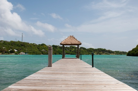 tropical wooden jetty with hut over sea in Long Bay, Antigua photo