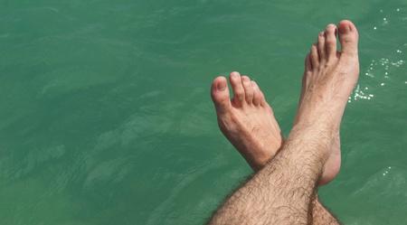 pies masculinos: relajante pies en el lago durante un día asoleado caliente (verano concepto de vacaciones)