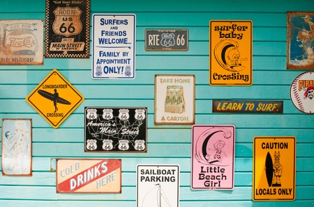 LONG BAY, WILLIKIES - AUGUST 20 2011: colorful antique signs on a blue wooden wall, surfing house on August 20, 2011 in Long Bay, ANTIGUA Editorial