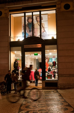 LISBON, PORTUGAL - DECEMBER 19: cyclist passing by at Benetton Boutique on December 19, 2011 in Lisbon, Portugal