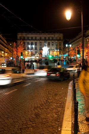 LISBON, PORTUGAL - DECEMBER 19: moving cars traffic and people in motion next to Luis Vaz de Cam�es square during Christmas time on December 19, 2011 in Lisbon, Portugal