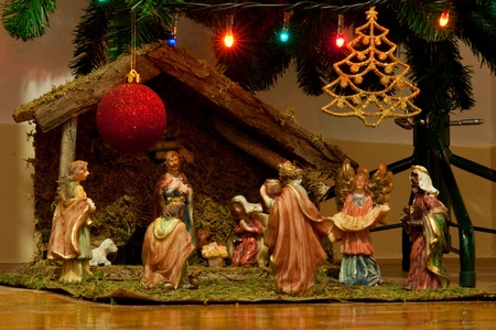 christmas nativity scene with hand-colored ceramic figures and below tree with many decorations (lights, bauble and star) photo