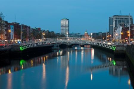 nightscene impresionante con Ha'penny puente y el río Liffey, el hito de la Aduana en el fondo (foto tomada después del atardecer)