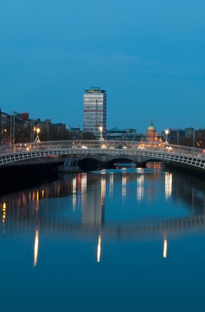 liffey: stunning nightscene with Hapenny bridge and Liffey river, the Custom House landmark at the background (picture taken after sunset)