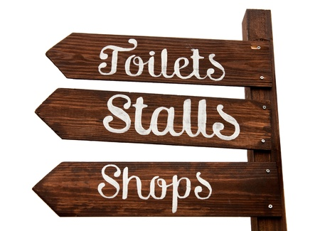wooden signage indicating toilets, stalls and shopping area (isolated on white background) photo