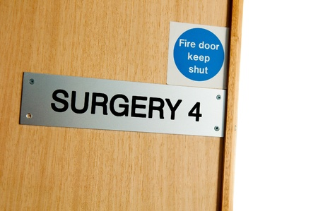 pratice: surgery sign at a wooden door (copy-space available, isolated on white) Stock Photo