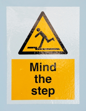mind the step caution sign on a blue wall background photo